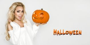 Beautiful young woman in white sweater, standing on white background and holding pumpkin;. Beautiful young blond sexy woman model in white sweater, standing on Royalty Free Stock Photos