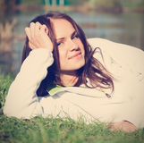 Beautiful young woman in a white sweatshirt lying on the grass Stock Photos