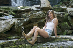 Beautiful young woman in white tank top and denim. Beautiful young Caucasian woman sits in front of waterfall wearing white tank-top and denim shorts - country Royalty Free Stock Images