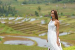 Beautiful young woman in White vintage dress stands in a half-turn on the background of rice fields. Close up stock image