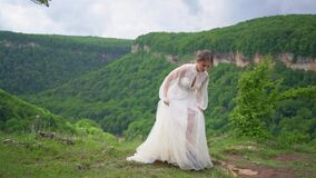 A young woman in a wedding dress and black boots jumps in the mountains.