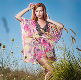 Beautiful young woman in wild flowers field on blue sky background. Portrait of attractive red hair girl with long hair relaxing Stock Image