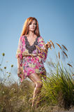 Beautiful young woman in wild flowers field on blue sky background. Portrait of attractive red hair girl with long hair relaxing Royalty Free Stock Photography