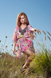 Beautiful young woman in wild flowers field on blue sky background. Portrait of attractive red hair girl with long hair relaxing Royalty Free Stock Photos