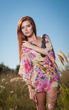 Beautiful young woman in wild flowers field on blue sky background. Portrait of attractive red hair girl with long hair relaxing Stock Photos