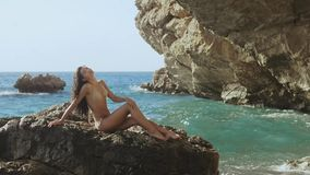 Beautiful young woman on wild rocky beach. stock footage