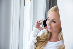 A beautiful young woman in the window Royalty Free Stock Photo