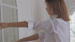 Beautiful young woman at the window in a white shirt. Dncing and relaxing in the dance hall stock video footage