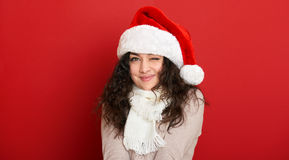 Beautiful young woman wink, portrait in santa helper hat and posing on red Stock Photos