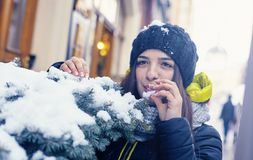 Beautiful young woman in winter. Beautiful young woman smiles, having tried the snow to taste Stock Photography