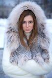Beautiful young woman in winter fur coat Stock Images