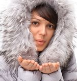 Beautiful young woman in winter jacket making a kiss. Closeup.portrait of beautiful young woman in winter jacket making a kiss Stock Photos