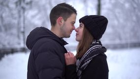 Portrait cute young woman in winter park under falling snow. Happy couple in love enjoys time together. Winter leisure stock video