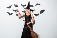 Beautiful young woman in witch costume with hat and broom. Beautiful young woman in black witch costume with hat and broom standing over white background stock image