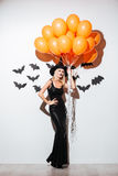 Beautiful young woman in witch halloween costume holding orange balloons Royalty Free Stock Photo