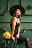 Beautiful young woman in witches hat and costume holding pumpkin. stock photography