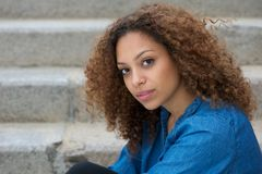 Beautiful Young Woman With Curly Hair Sitting Outdoors Stock Photo