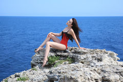 Free Beautiful Young Woman With Flying Hair In Red Bathing Suit Sitting On The Rocks Stock Photography - 86428682