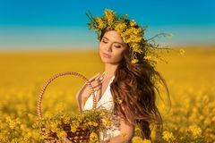 Beautiful Young Woman With Wreath On Long Healthy Hair Over Yellow Rape Field Landscape Background. Attracive Brunette Girl With Stock Image