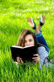 Beautiful young woman woman reading a book in a park Royalty Free Stock Photography