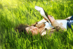 Beautiful young woman woman reading a book in a park Stock Photography