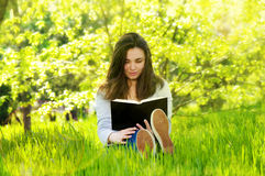 Beautiful young woman woman reading a book in the park Royalty Free Stock Photos