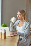 Beautiful young woman working with computer at cafe, holding a cup of drink Royalty Free Stock Photos