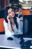 Beautiful young woman working on computer and talking on phone Stock Image
