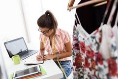 Beautiful young woman working in designer studio. Stock Photo