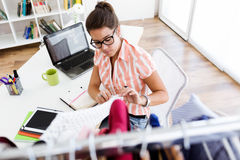 Beautiful young woman working in designer studio. Royalty Free Stock Images