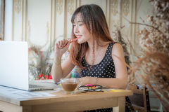 The beautiful young woman working on her laptop in her office Royalty Free Stock Image