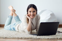 Beautiful young woman working on her laptop at home. Stock Photos