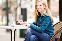 Beautiful young woman working on her laptop at an outdoor cafe Royalty Free Stock Photography