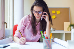Beautiful young woman working in her office. Royalty Free Stock Images