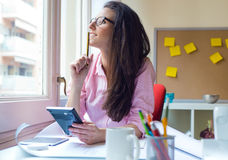 Beautiful young woman working in her office. Portrait of beautiful young woman working in her office Stock Photos