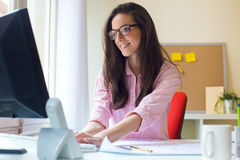 Beautiful young woman working in her office. Stock Images