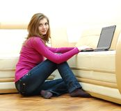 Beautiful young woman working on a laptop. On the floor at home Royalty Free Stock Images