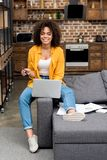 Beautiful young woman working with laptop on couch royalty free stock photo