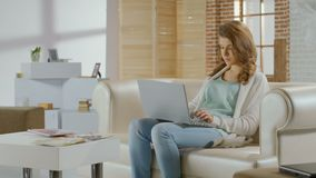 Beautiful young woman working on laptop in modern apartment. Stock footage stock video