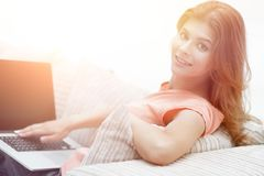 Beautiful young woman working with laptop sitting on sofa and looking at camera. Young woman working with laptop sitting on sofa and looking at camera.photo Stock Image