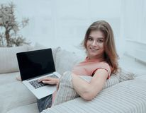 Beautiful young woman working with laptop sitting on sofa and looking at camera. Young woman working with laptop sitting on sofa and looking at camera.photo Royalty Free Stock Photos