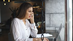 Beautiful young woman working with laptop and talking on smartphone talking to customer sitting near window. Young businesswoman dressed in white shirt is stock video footage