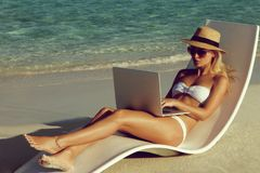 Beautiful young woman working with laptop on the tropical beach stock image