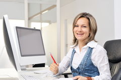 Beautiful young woman working at the office. Beautiful happy young woman working at the office Stock Photography
