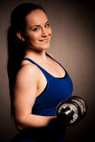 Beautiful young woman working out with dumbels in fitness gym. Beautiful young woman working out with dumbels in a fitness gym Royalty Free Stock Photo