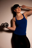 Beautiful young woman working out with dumbels in fitness gym Stock Image