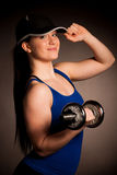 Beautiful young woman working out with dumbels in fitness gym. Beautiful young woman working out with dumbels in fitness Stock Photos