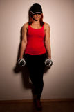 Beautiful young woman working out with dumbels in fitness gym. With hat on head Stock Photography