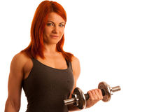 Beautiful young woman working out with dumbels in fitness gym. Isolated Stock Photography