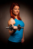 Beautiful young woman working out with dumbels in fitness gym Royalty Free Stock Images